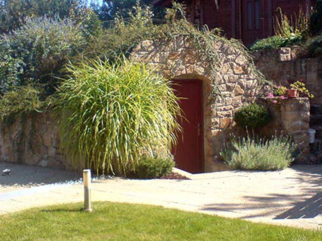 Wine cellar in the garden hidden under the roof planting