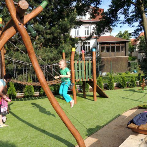 Children in the new playground made of acacia wood and artificial grass