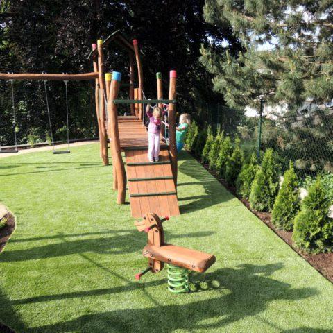 Children's playground with artificial grass in the garden